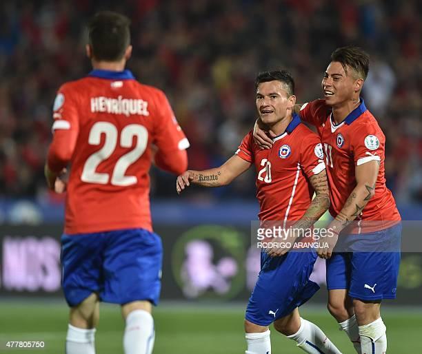 cChile's midfielder Charles Aranguiz celebrates with teammates Eduardo Vargas and Angelo Henriquez after scoring against Bolivia during their 2015...