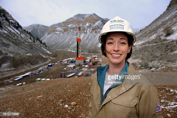 CD05WILDWELL01d EnCana oil and gas Inc Natural Resource Specialist Nicole M Byrnes near a drilling rig on a new pad in a valley of the EnCana Ranch...