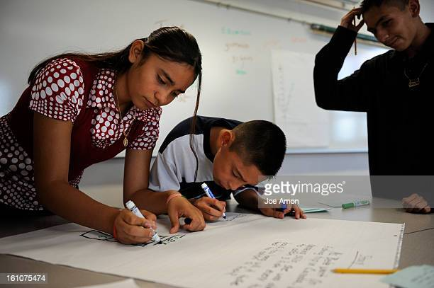 CD30CSAP28b Andrea Arellano 14 works on the first math problem of the year for the Bruce Randolph School 9th grader as her little brother Ramon...