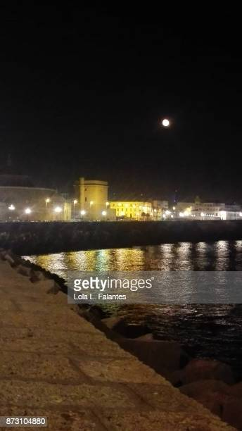 Cádiz cityscape at night, with the moon on the sky