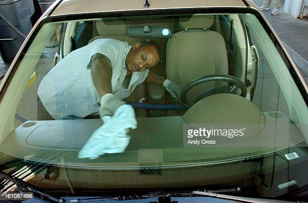 CDPROOFb--Ethiopian, Samuel Tafesa, 22-years-old, washes a car window at Hertz rental cars, DIA, Friday morning. Tafesa had to flea his country after...