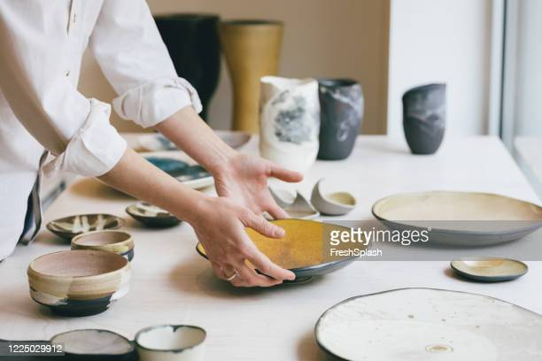 cearamic dishware at gallery, a handmade plate being put into a shop window - ceramics stock pictures, royalty-free photos & images