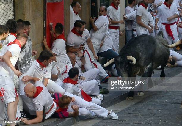 A Cebada Gago fighting bull looks at participants as it runs past them on the first day of the San Fermin bull run festival in Pamplona northern...
