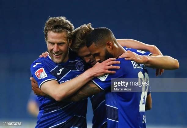 Cebio Soukou of Bielefeld celebrates scoring his team's fourth goal with Sven Schipplock and Fabian Kunze during the Second Bundesliga match between...