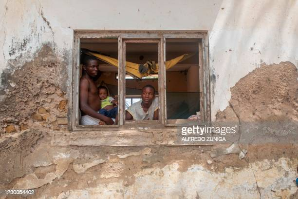 Cebo Saba , her young son and her nephew Rashide Silva look on December 10, 2020 from a window of an abandoned warehouse in the Napala Agrarian...