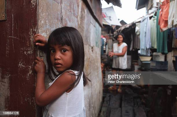 Cebu City Cebu Philippines A young girl stands outside her parents' wooden squatter house in a slum area There are millions of impoverished people...