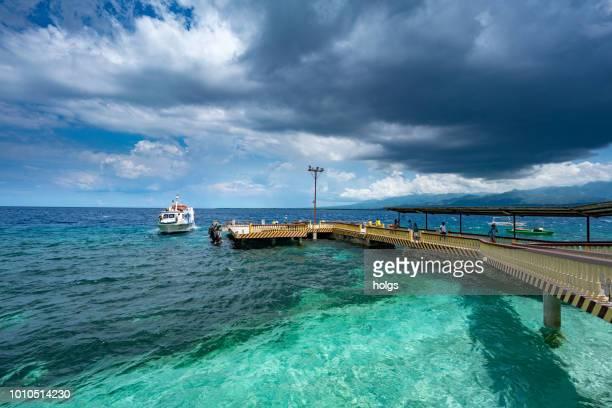 moalboal cebu bereich durch boote und menschen zu fuß auf die brücke am strand - cebu stock-fotos und bilder