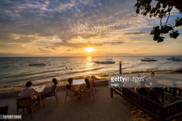 moalboal cebu bereich durch boote auf den strand und die menschen entspannen am strand bei sonnenuntergang - cebu stock-fotos und bilder