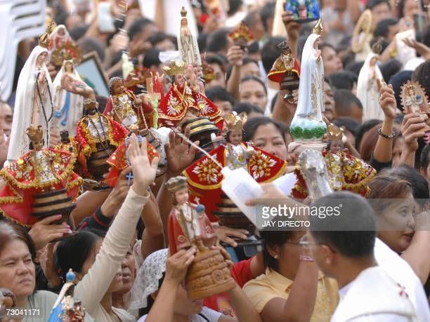 A priest blesses devotees and the religious icons as they attend a mass at the Basilica Del Santo Nino in Cebu city 19 January 2007 The mass is part...