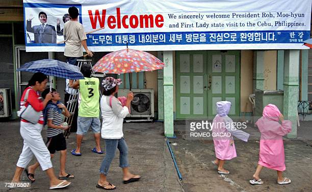 A worker hangs a welcome banner for the South Korean President Roh Moohyun on a facade of a Korean restaurant in Cebu city in central Philippines...