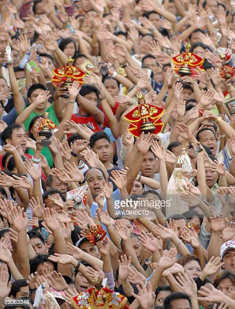 Devotees attending a mass raise their hands in prayer as they hold a religious icon of the Santo Nino at the Basilica Del Santo Nino in Cebu city 19...
