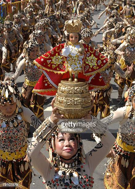Performers dancing in the street holding a religious icon of the Santo Nino during the culmination of the nineday religious festival called Sinulog...