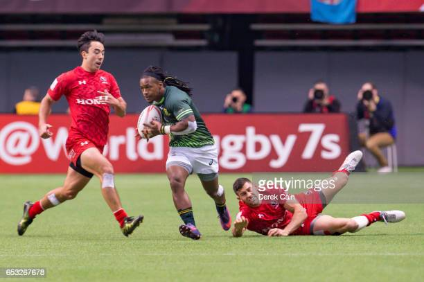 Cecil Afrika of South Africa breaks free from a tackle by Justin Douglas of Canada during day 2 of the 2017 Canada Sevens Rugby Tournament on March...