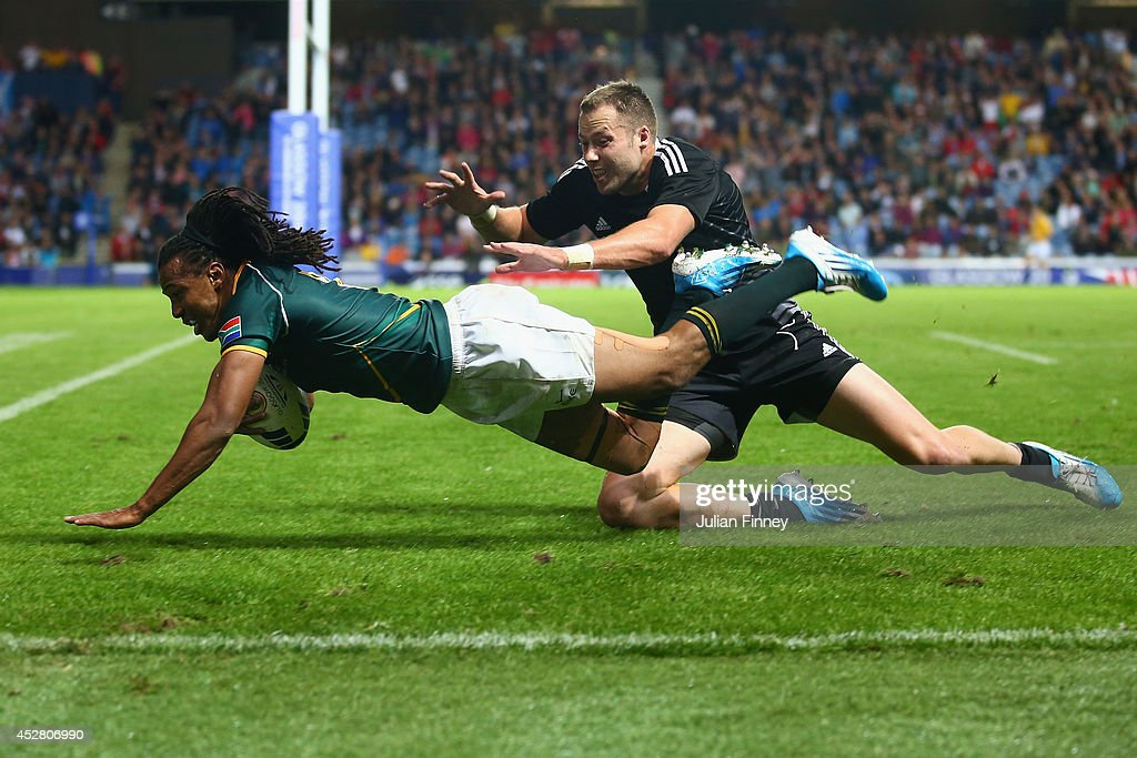 Cecil Afrika of South Africa jumps to score a try during the final match between South Africa and New Zealand at Ibrox Stadium during day four of the Glasgow 2014 Commonwealth Games on July 27, 2014 in Glasgow, United Kingdom.
