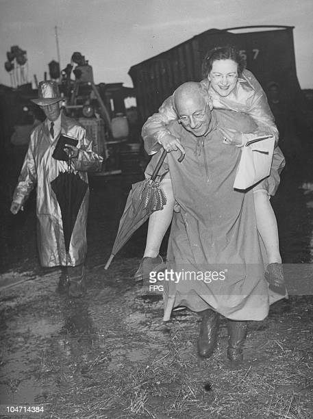 Cecil B deMille American film director giving a piggyback ride to his secretary Gladys Rosson who is carrying an umbrella as they visit the circus in...