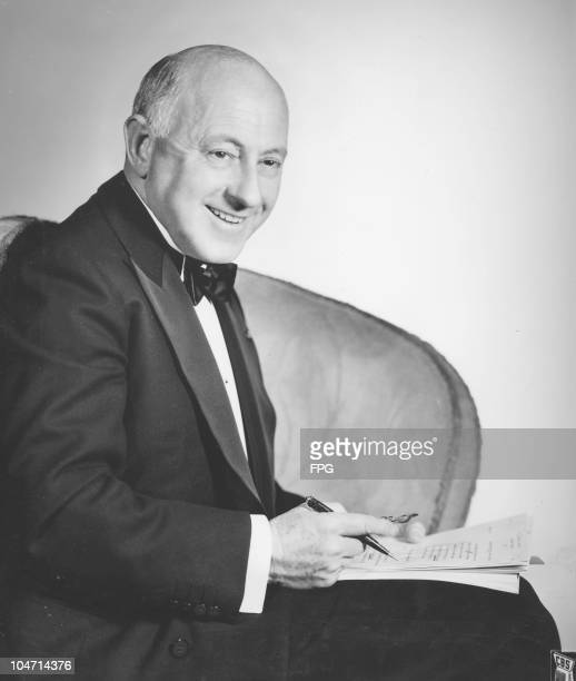 Cecil B deMille American film director smiling and wearing a tuxedo with bow tie circa 1930 DeMille poses with a script and a pen in his right hand