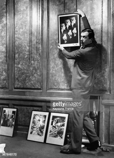 Cecil Beaton accrochant une photographie pour son expostion de photographies et peintures à la Cooling's Gallery à Londres RoyaumeUni le 24 novembre...