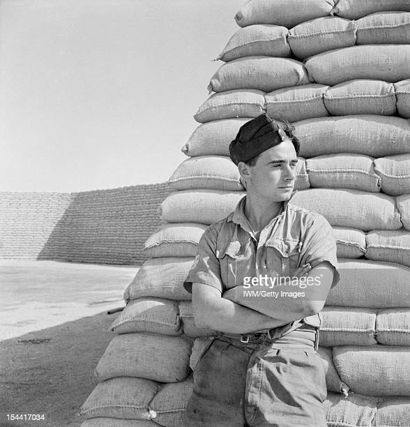 General The Western Desert 1942 A Royal Air Force officer wearing a cap with his arms folded portrayed against the sandbags which were the universal...