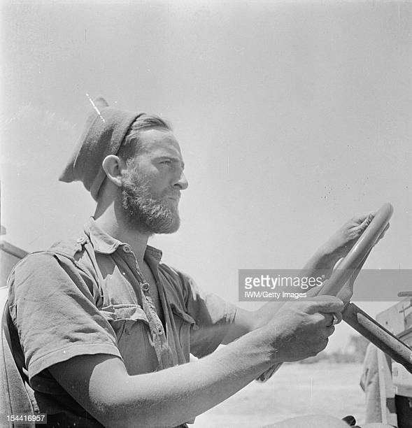 General The Western Desert 1942 Head and shoulders portrait of a bearded member of the Long Range Desert Group wearing a woolly cap at the wheel of...