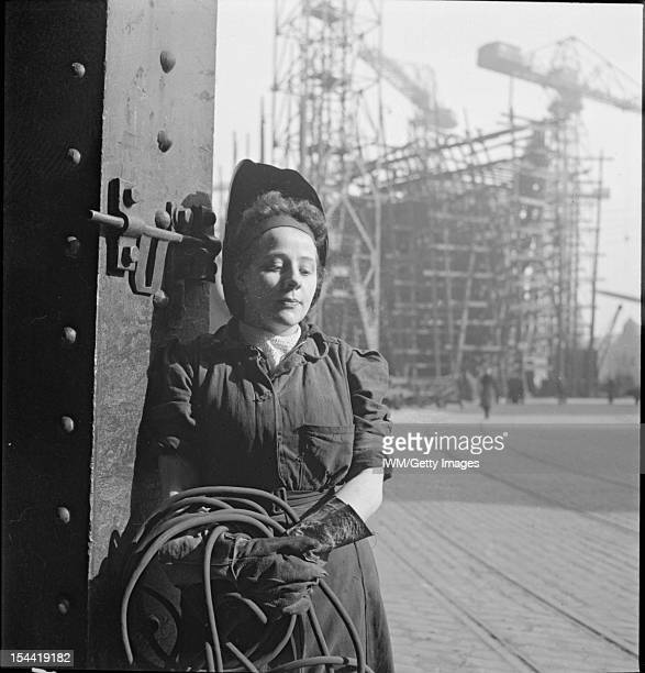 Tyneside Shipyards A study of a young woman welder She is posing for the photographer leaning against a column In the background a ship under...