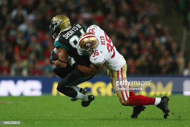 Cecil Shorts III of the Jacksonville Jaguars is tackled by Eric Reid of the San Francisco 49ers during the NFL International Series game between San...
