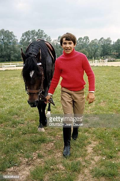 Cecile Aubry And Her Son Mehdi. A Saint-Cyr-sous-Dourdan, en mai 1970, MEDHI, en pull rouge, tire son cheval pur-sang 'Roi d'Atout' par les rênes.