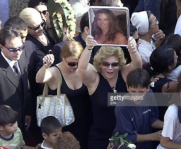 Cecilia Cubas aunt holds a portrait of her niece during Cecilia's burial at the Italian cemetery in Asuncion 18 February 2005 Five months after she...