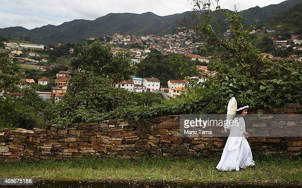 Cecilia Elena Moraes walks home while being photographed by her family after marching in the annual Easter procession during traditional Semana Santa...