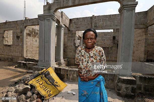 Cecilia Labara a local resident poses for a photograph outside her new house construction funded with compensation money paid to the people of Bodo...