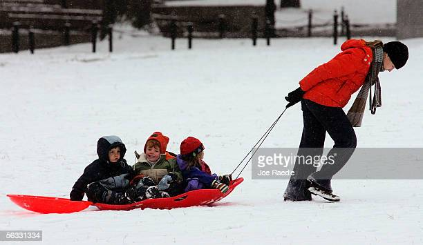 Cecilia Rait pulls her children to a hill for sledding in a few inches of snow on the Boston Common December 4, 2005 in Boston, Massachusetts. Total...