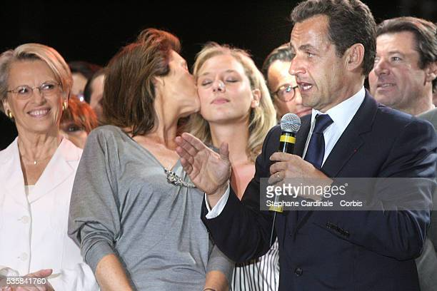 Cecilia Sarkozy kisses her daughter as her husband Union for a Popular Movement party leader and president elect Nicolas Sarkozy addresses his public...
