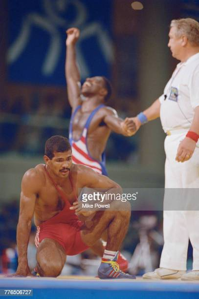 Cecilio Rodríguez of Cuba kneels on the floor as Rodney Smith of the United States celebrates behind him after Smith beat Rodriguez to win the bronze...