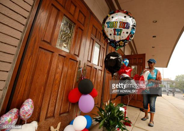 Ceclily McClellan places flowers and baloons at the door of New Bethel Baptist Church after it was announced Aretha Franklin had passed away on...