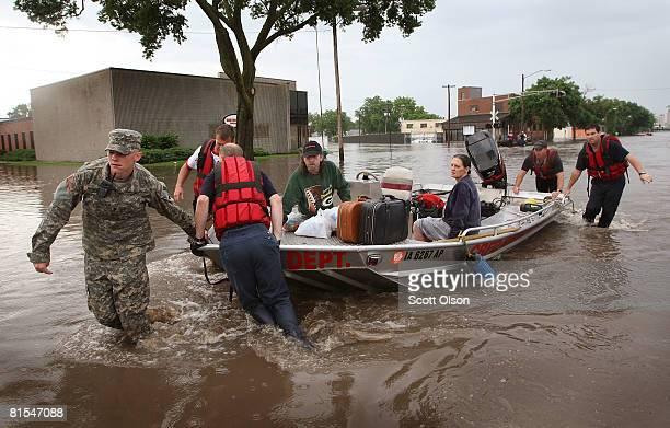 Cedar Rapids Fire Department personnel and Army reservists use a boat to rescue residents from flooded areas of the city June 12, 2008 in Cedar...