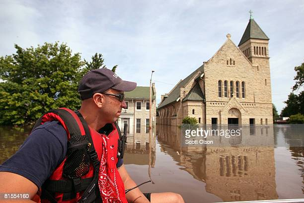 Cedar Rapids firefighter Jason Lopez patrols a flooded street looking for stranded residents June 13, 2008 in Cedar Rapids, Iowa. The city continues...