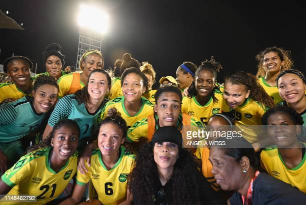 Cedella Marley poses with Jamaica Women's football team 'Reggae Girlz' after the friendly football match Jamaica vs Panama at the National Stadium in...