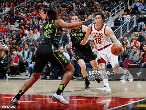 Cedi Osman of the Cleveland Cavaliers drives against Isaiah Taylor and Mike Muscala of the Atlanta Hawks at Philips Arena on February 9 2018 in...