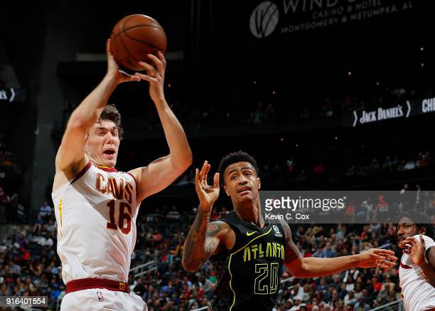 Cedi Osman of the Cleveland Cavaliers grabs a rebound against John Collins of the Atlanta Hawks at Philips Arena on February 9 2018 in Atlanta...