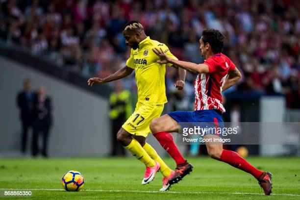 Cedric Bakambu of Villarreal CF is tackled by Stefan Savic of Atletico de Madrid during the La Liga 201718 match between Atletico de Madrid and...