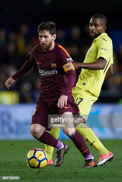 Cedric Bakambu of Villarreal competes for the ball with Lionel Messi of Barcelona during the La Liga match between Villarreal and Barcelona at...