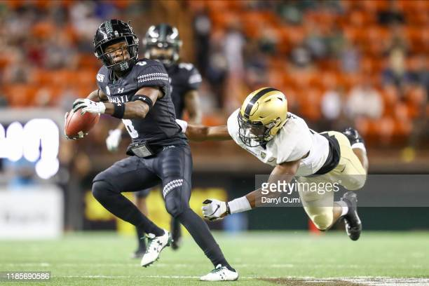 Cedric Byrd II of the Hawaii Rainbow Warriors dodgers a diving Malkelm Morrison of the Army Black Knights during the third quarter of the game at...