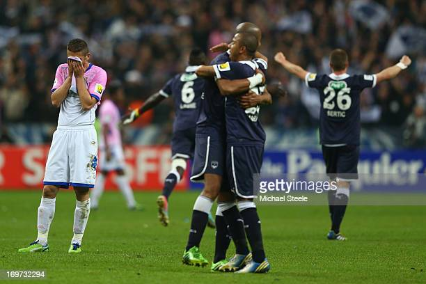 Cedric Cambon of Evian Thonon Gaillard is dejected at the final whistle as Ludovic Sane and Mariano Ferreira Filho of Bordeaux celebrate their sides...