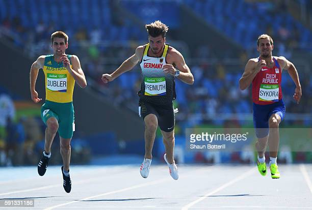 Cedric Dubler of Australia Rico Freimuth of Germany and Jiri Sykora of the Czech Republic compete in the Men's Decathlon 100m heats on Day 12 of the...