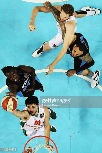 Cedric Jackson of the Breakers defends as Todd Blanchfield of the Crocodiles lays the ball up during game three of the NBL Finals series between the...