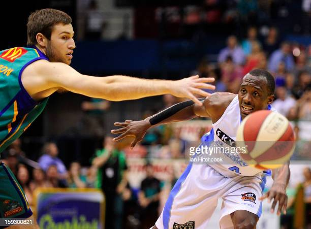 Cedric Jackson of the Breakers passes the ball past Mitch Norton of the Crocodiles during the round 14 NBL match between the Townsville Crocodiles...
