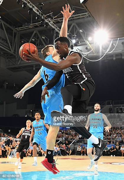 Cedric Jackson of United passes behind the back of Kirk Penny of the Breakers during the round five NBL match between Melbourne United and the New...