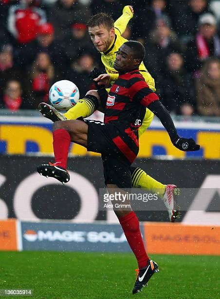 Cedric Makiadi of Freiburg is challenged by Jakub Blaszczykowski of Dortmund during the Bundesliga match between SC Freiburg and Borussia Dortmund at...