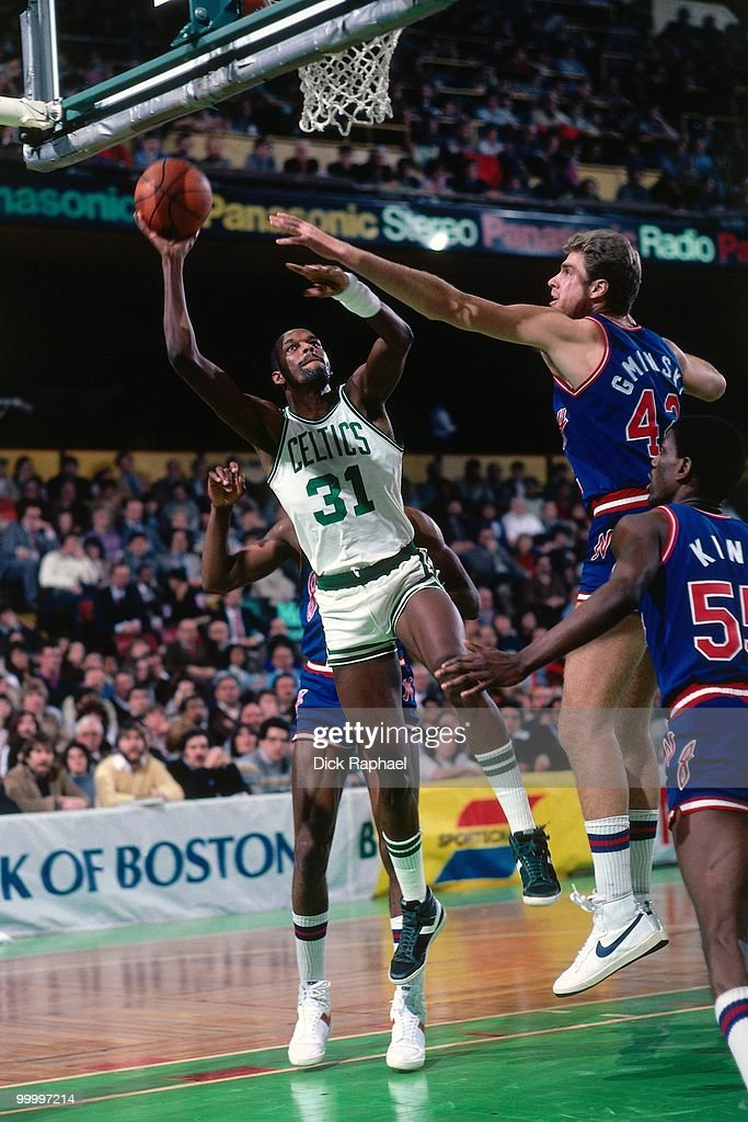 Cedric Maxwell #31 of the Boston Celtics goes up for a shot against Mike Gminski #43 of the New Jersey Nets during a game played in 1983 at the Boston Garden in Boston, Massachusetts.