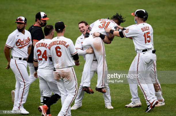 Cedric Mullins of the Baltimore Orioles celebrates with teammates after driving in the game winning run with a sacrifice fly in the tenth inning...