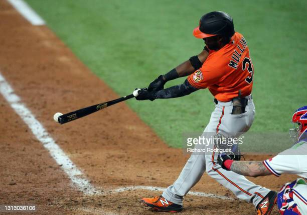 Cedric Mullins of the Baltimore Orioles hits an RBI single in the seventh inning against the Texas Rangers during the MLB game at Globe Life Field on...
